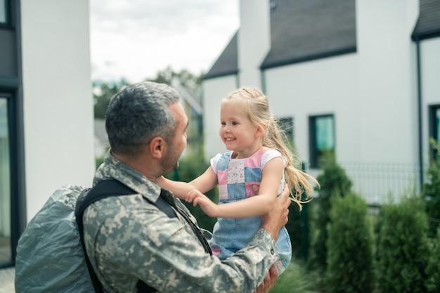 Tochter lächelt. fröhliche blonde tochter lächelt, während sie papa nach dem militärdienst ansieht