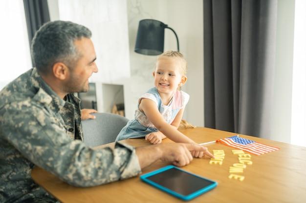 Tochter lächelt. süße dunkeläugige tochter, die lächelt, während sie papa sieht, der zu hause eine militäruniform trägt