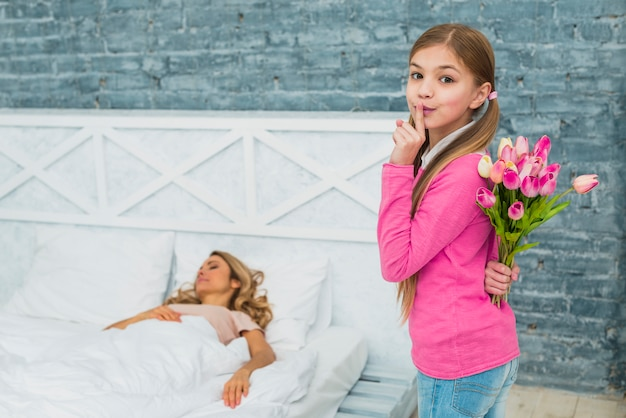 Tochter mit den tulpen, die finger auf den lippen halten