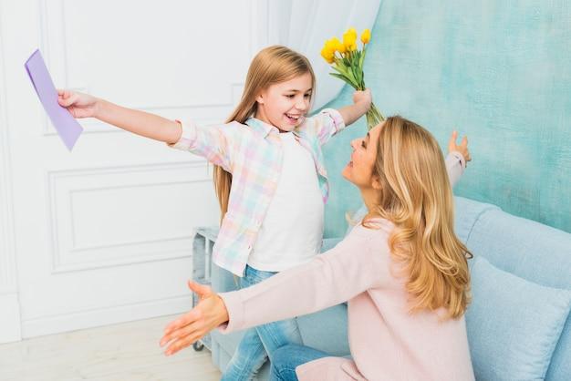 Tochter mit geschenkenblume und -postkarte, die mutter umarmen
