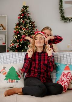Tochter setzt weihnachtsmütze auf erfreuten mutterkopf, der auf couch sitzt und weihnachtszeit zu hause genießt