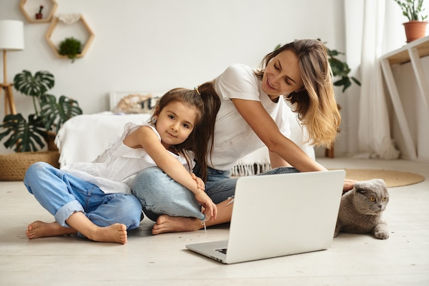 Tochter spielt mit mama und katze, während mama am computer arbeitet