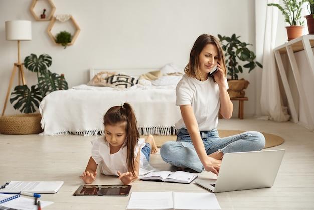 Tochter spielt mit mutter und katze, während mutter am computer arbeitet