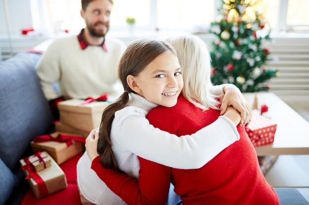 Tochter umarmt ihre mutter am weihnachtstag