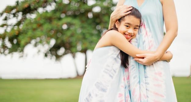 Tochter umarmt ihre mutter im park