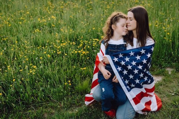 Tochter umarmt mutter in amerikanische flagge gehüllt
