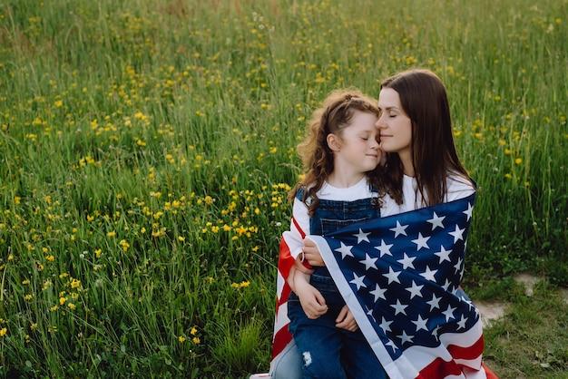 Tochter umarmt mutter mit der flagge der vereinigten staaten von amerika