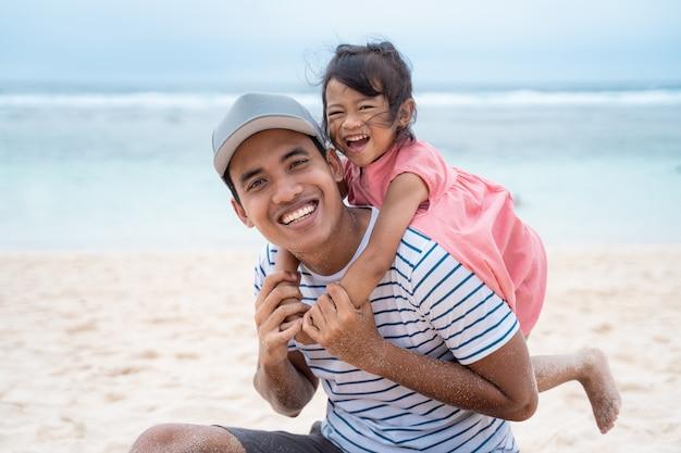 Tochter umarmt seinen vater von hinten beim spielen