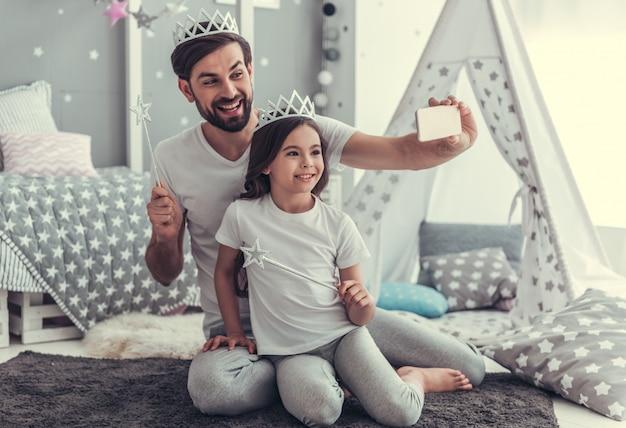 Tochter und ihr junger vater in kronen machen selfies.