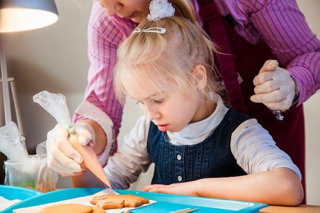 Tochter und mutter dekorieren lebkuchen mit zuckerglasur