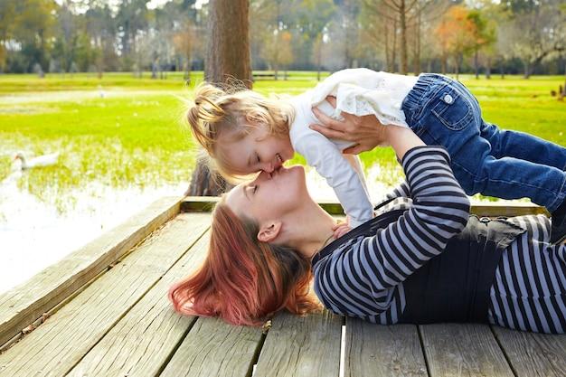 Tochter und mutter, die zusammen im park spielen
