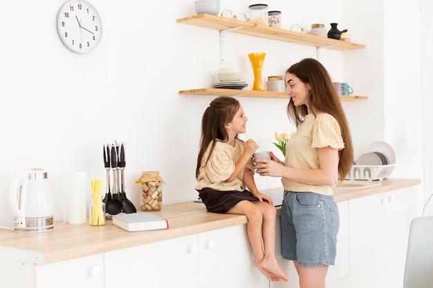 Tochter und mutter haben einen süßen moment in der küche