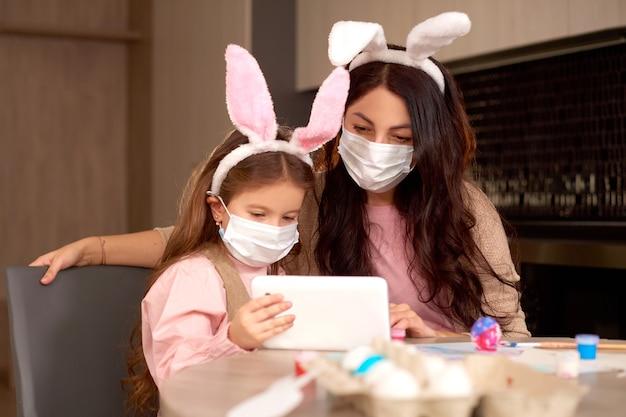 Tochter und mutter in medizinischer maske senden videobotschaft an verwandte mit tablet-gerät. familie feiern ostern zu hause in quarantäne online