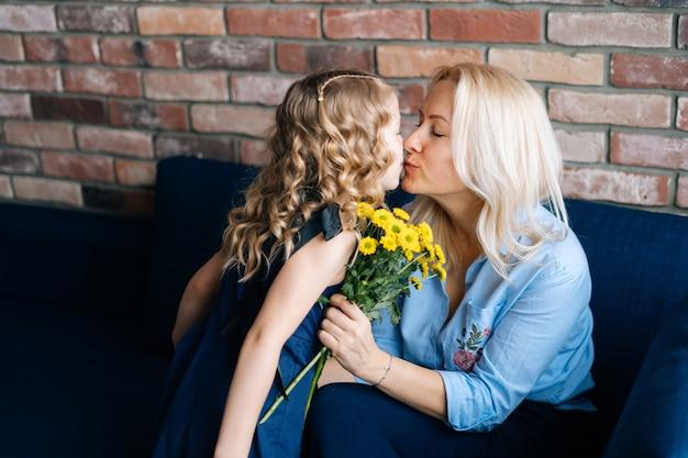 Tochter und mutter küssen sich in ihrem haus mädchen gibt mutter einen blumenstrauß