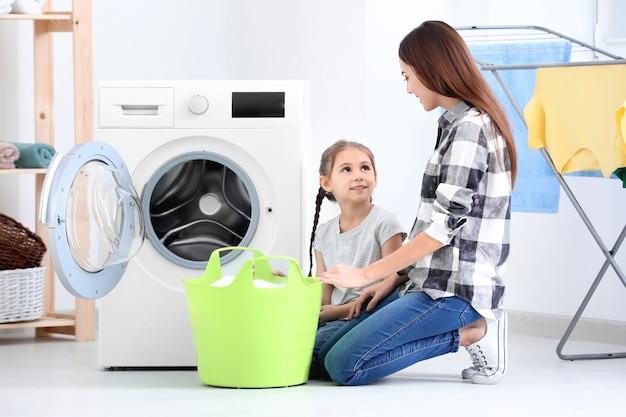 Tochter und mutter machen zu hause gemeinsam wäsche