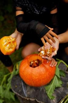 Tochter- und mutterhände, die samen und fasermaterial aus einem kürbis ziehen, bevor sie für halloween schnitzen, bereiten jack o'lantern vor. dekoration für party, kleiner familienhelfer,