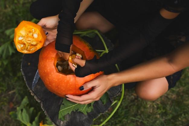 Tochter- und mutterhände, die samen und fasermaterial aus einem kürbis ziehen, bevor sie für halloween schnitzen, bereiten jack o'lantern vor.