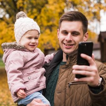 Tochter und vater, die selfie im herbstpark machen