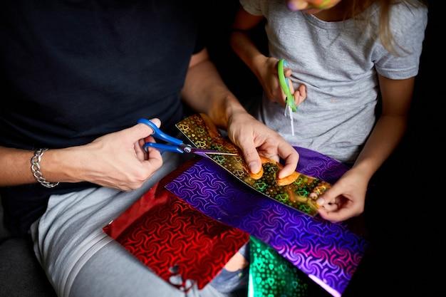 Tochter und vater haben spaß daran, gemeinsam zu hause auf dem sofa zu basteln, ein papier mit einer schere zu schneiden, dunkles licht,
