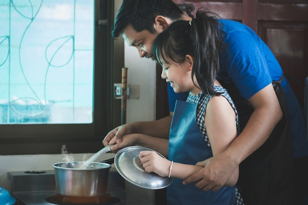 Tochter und vater kochen glücklich zusammen in der küche. familienkochkonzept
