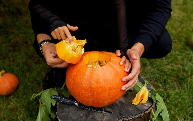 Tochter und vater öffnen die hände, schneiden kürbis, bevor sie für halloween schnitzen, bereitet jack o'lantern vor. dekoration für party, kleiner familienhelfer, draufsicht, nahaufnahme, ansicht von oben, kopierraum