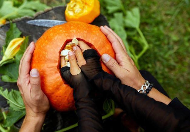 Tochter- und vaterhände ziehen samen und faserigen kürbis, bevor sie für halloween schnitzen, bereitet jack o'lantern vor. dekoration für party, kleiner familienhelfer, draufsicht, nahaufnahme ,, kopierraum