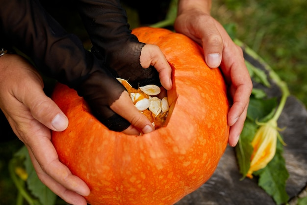 Tochter- und vaterhände ziehen samen und fasermaterial von einem kürbis, bevor sie für halloween schnitzen. draufsicht, nahaufnahme, ansicht von oben, kopierraum