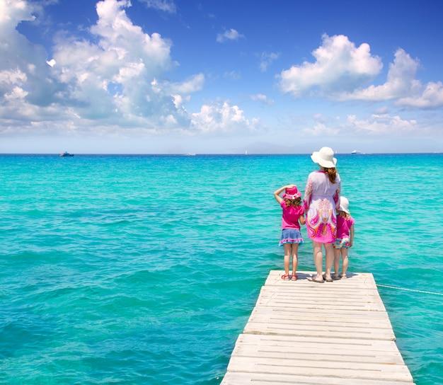 Töchter und mutter in anlegestelle am tropischen strand