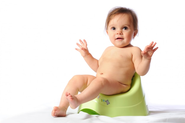 Töpfchentraining des entzückenden lustigen babyporträts auf lokalisiertem weiß.