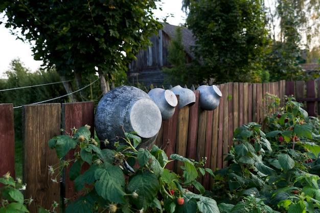 Töpfe für einen rustikalen holzofen, trocknen auf einer rustikalen holzpalisade. vor dem hintergrund eines alten holzhauses. foto in hoher qualität
