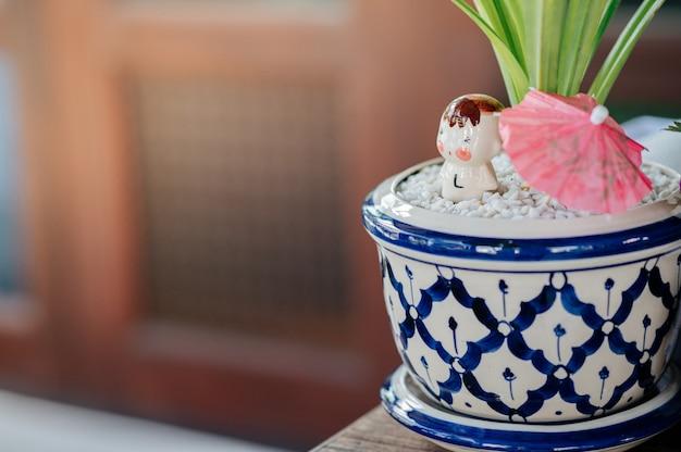 Töpfe mit schönen mustern und dekorativen gegenständen wie weißem stein, steinpuppen, kleinen regenschirmen