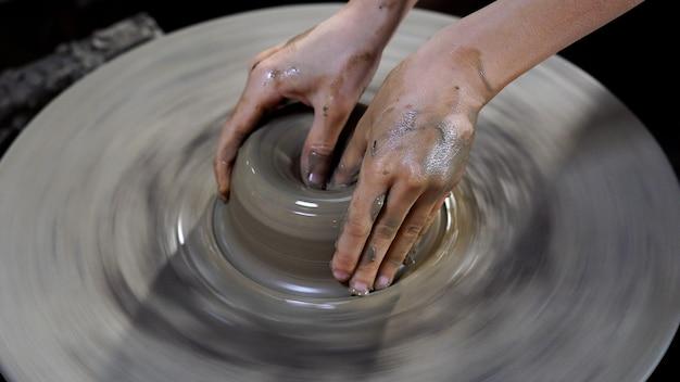 Töpferhände stellen ein glas oder eine vase mit steingut auf dem rad her