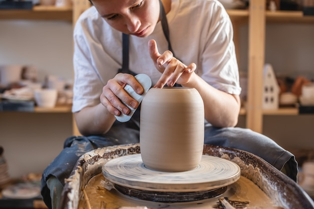 Töpferin, die an einer töpferscheibe arbeitet, die eine vase macht