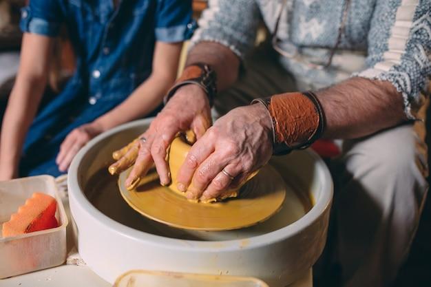 Töpferwerkstatt. opa unterrichtet enkelin keramik. tonmodellierung