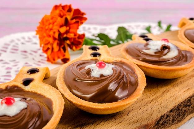 Törtchen in form von löffeln, mit süßer schokoladenhaselnusspaste auf einem schneidebrett.