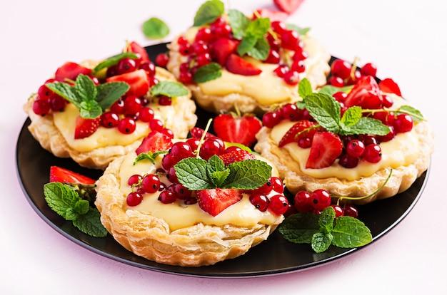 Törtchen mit erdbeeren, johannisbeeren und schlagsahne, dekoriert mit minzblättern.