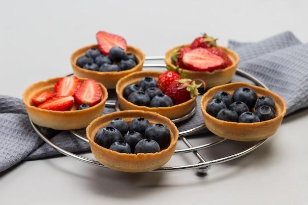 Törtchen mit erdbeeren und blaubeeren auf metallständer Premium Fotos