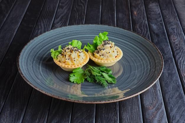 Törtchen mit kartoffelpüree, frischkäse und eingelegter gurke. vorspeise für den empfang