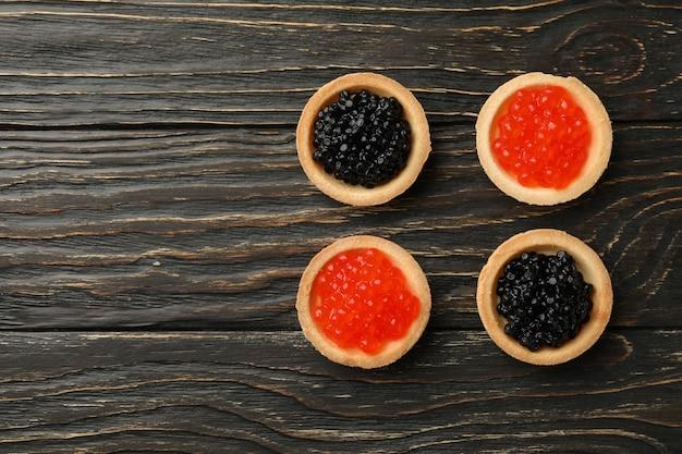 Törtchen mit rotem und schwarzem kaviar auf holz