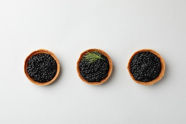Törtchen mit schwarzem kaviar auf weißer draufsicht