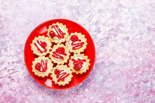 Törtchen mit weißer schokoladenfüllung und beerenmarmelade.
