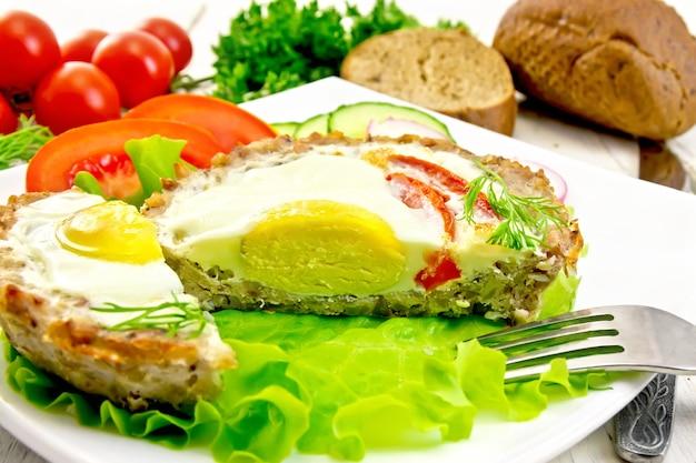 Törtchenfleisch mit ei und tomate in den teller geschnitten auf salat, brot und dill auf den hellen holzbrettern des hintergrundes