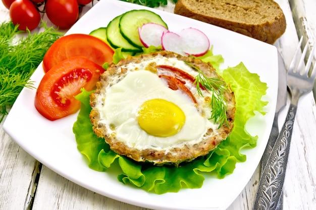 Törtchenfleisch mit ei und tomate in der platte auf salat, brot und dill auf den hellen holzbrettern des hintergrundes