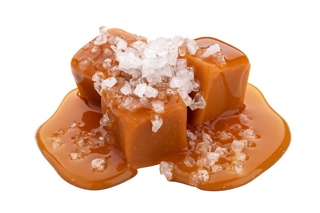 Toffee-bonbons mit geschmolzener karamellsauce und salz isoliert auf weiß
