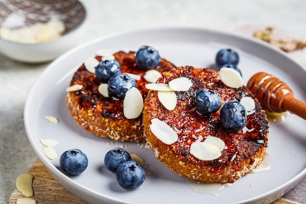 Tofu-pfannkuchen mit blaubeeren und honig auf grauem teller. gesundes veganes lebensmittelkonzept.