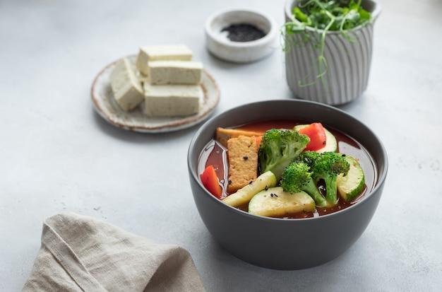 Tofu-suppe mit brokkoli-zucchini-paprika in dunkler schüssel gesunder veganer asiatischer lebensmittelkopierraum