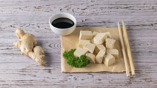 Tofukäse mit ingwerwurzel, kräutern und sojasauce auf einem holztisch. sojakäse. vegetarisches produkt.