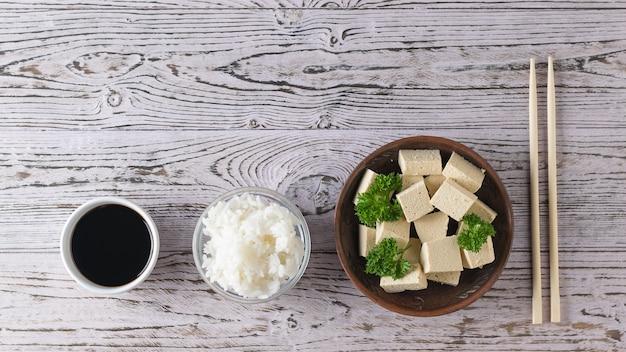 Tofukäse mit petersilie, sojasauce und reis auf einem holztisch. sojakäse. vegetarisches produkt. flach liegen.