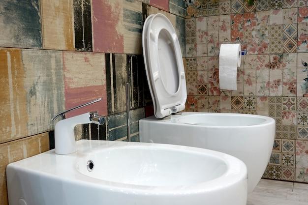 Toilette und bidet auf einem wandhintergrund mit einer farbigen fliese