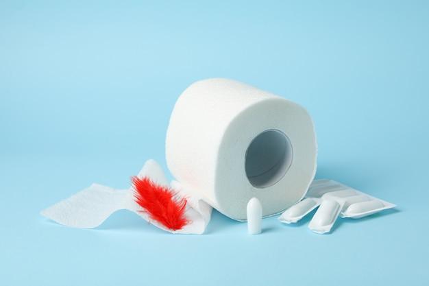 Toilettenpapier, federn und kerzen auf blau. hämorrhoiden